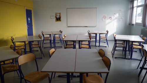 Tables disposées en îlots dans la classe.